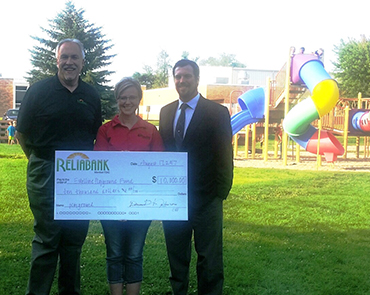 Reliabank CEO David W Johnson present a check to the Estelline School and Economic Development for new playground equipment